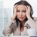 Büroangestellte mit Burnout an ihrem Schreibtisch