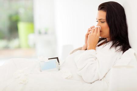 Erkältete Frau im Bett mit Schnupfen