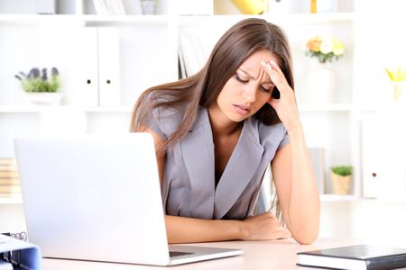 Eine Bürokauffrau mit Kopfschmerzen an ihrem Arbeitsplatz