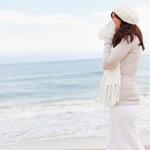 Eine Frau mit Heuschnupfen am Strand