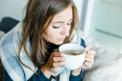 Frau mit Tee auf der Couch